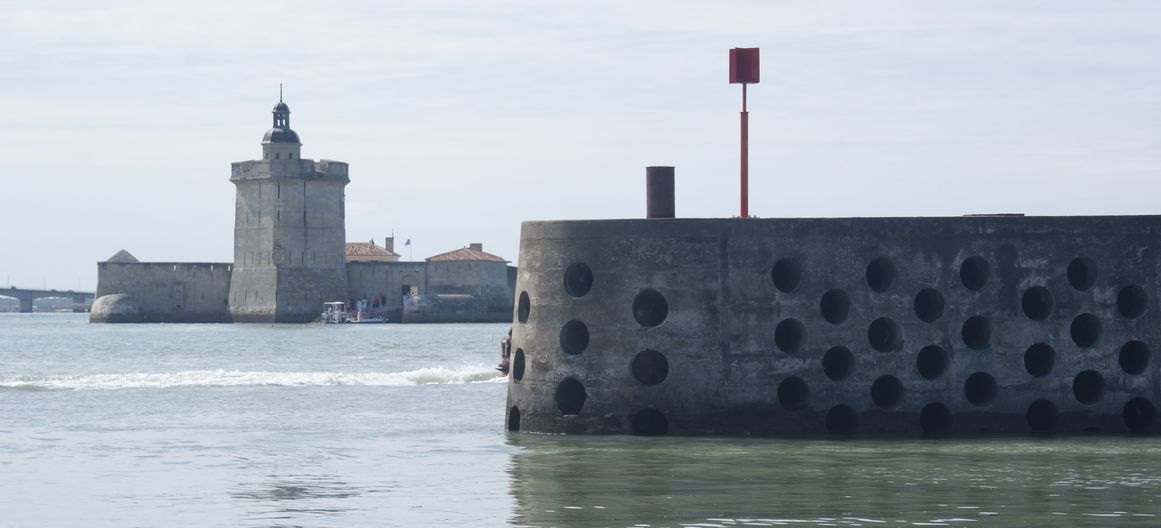The mole of the port of Bourcefranc-le-Chapus with, in the background, Fort Louvois where tide gauge observations were made nearby in the 19th and 20th centuries (Photo credits N. Pouvreau, August 2009)